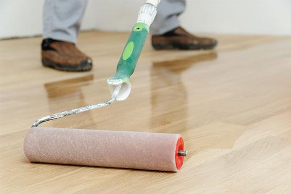 Roller applying finish to installed hardwood floor